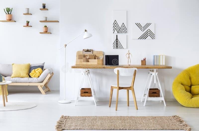 Intérieur moderne de siège social avec les graphiques, le bureau, le sofa et le pouf jaune photo libre de droits