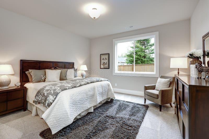 Intérieur moderne léger de chambre à coucher principale avec le lit et la raboteuse de darkwood photos libres de droits