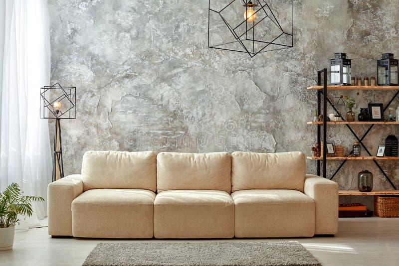 Intérieur moderne salon aux murs gris, canapé beige, lampe de sol et lustre, étagère de moquette claire avec cadres photo stock