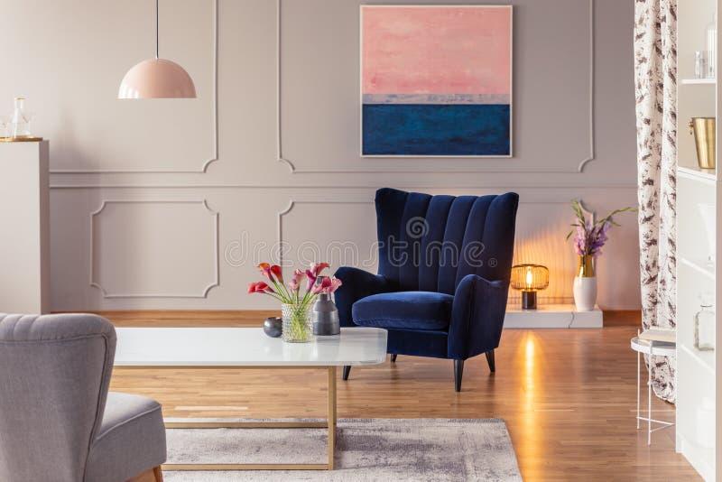 Intérieur romantique de salon avec un fauteuil, une peinture, une lumière confortable et des fleurs image libre de droits