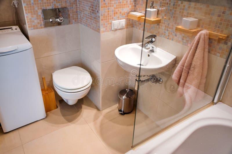 Intérieur simple moderne en appartements légers Intérieur de salle de bains avec la douche et le miroir en verre de porte photographie stock
