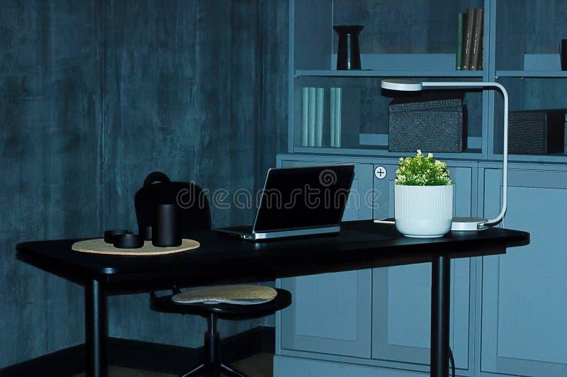 Intérieur Une table noire avec un ordinateur portable dans une chambre avec les murs gris en béton photo stock