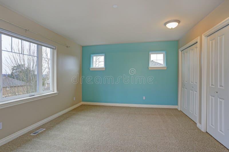 Intérieur vide léger de pièce avec le foyer sur un mur bleu lumineux photographie stock libre de droits
