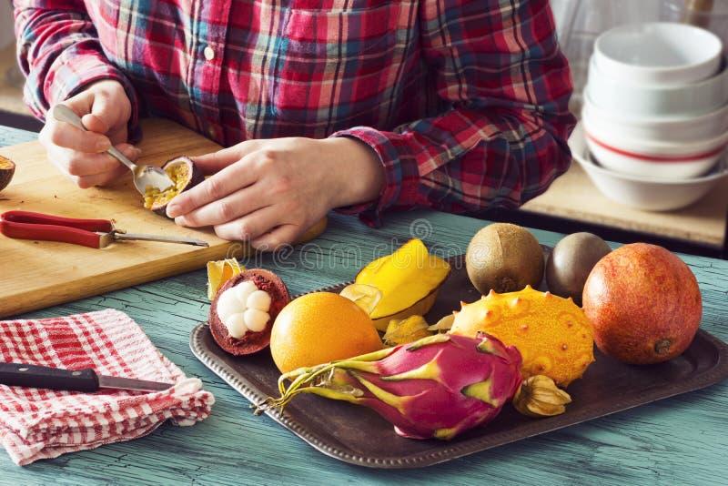 Intérieurs de excavation de femme de Passionfruit tout en préparant la salade de fruits tropicale images stock