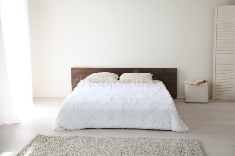 Intérieurs lumineux de chambre à coucher blanche avec le lit image libre de droits