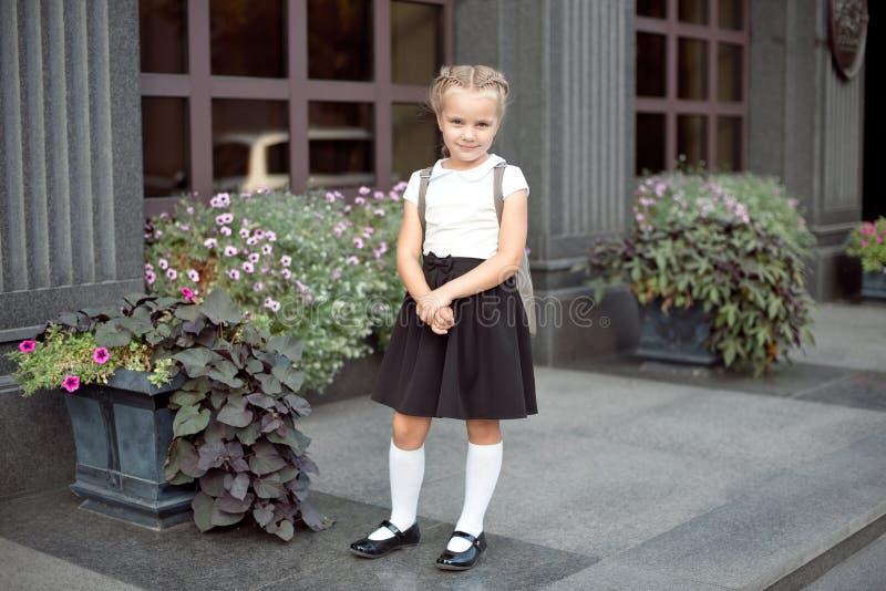 Int?gral d'une petite fille de sourire dans l'uniforme scolaire posant sur un fond d'entr?e d'?cole photographie stock