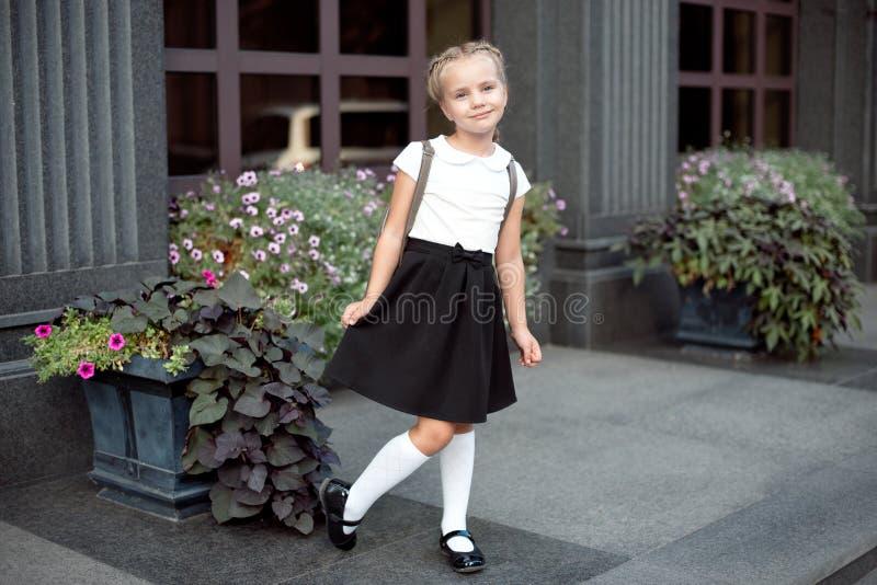 Int?gral d'une petite fille de sourire dans l'uniforme scolaire posant sur un fond d'entr?e d'?cole photo stock