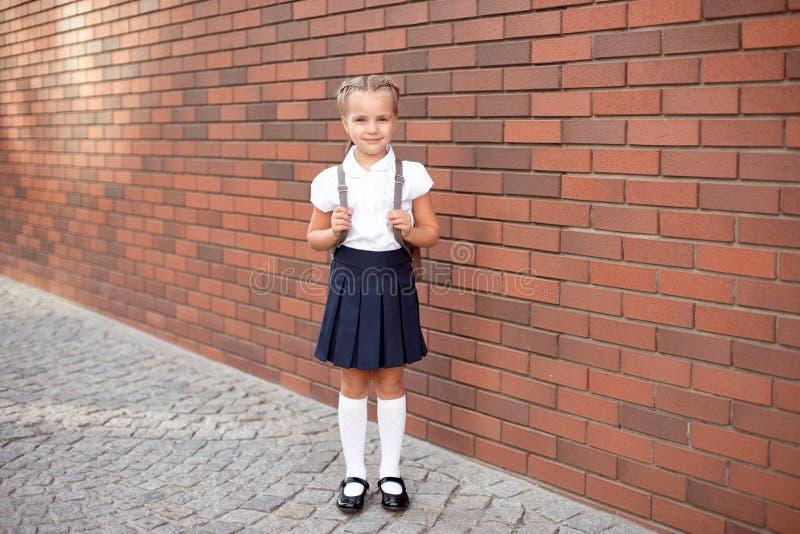 Int?gral d'une petite fille de sourire dans l'uniforme scolaire posant sur un fond d'entr?e d'?cole images libres de droits