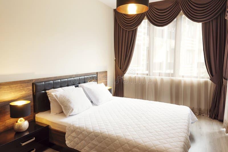 Int?rieur de chambre ? coucher moderne avec le double lit confortable Windows avec de longs rideaux, draperie et cisaillements Ph photos libres de droits