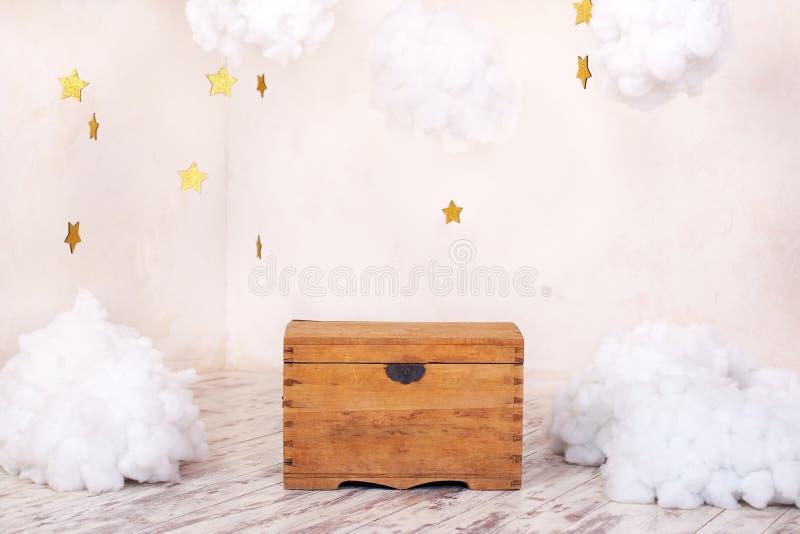 Int?rieur moderne de cru de la pi?ce d'enfants avec un vieux coffre en bois sur le fond d'un mur texturis? avec des nuages ` S p  photo libre de droits