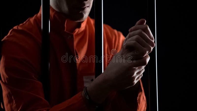 Intagen i handbojor som gnider handleder, omänskliga villkor och tortyr i fängelse arkivbild