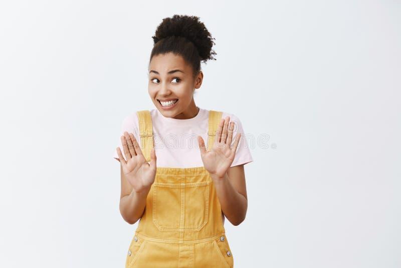 Inte allt som är fint egentligen Intensiv bekymrad och nervös gullig afrikan som är kvinnlig i gula overaller som tillbaka stoppa royaltyfri fotografi
