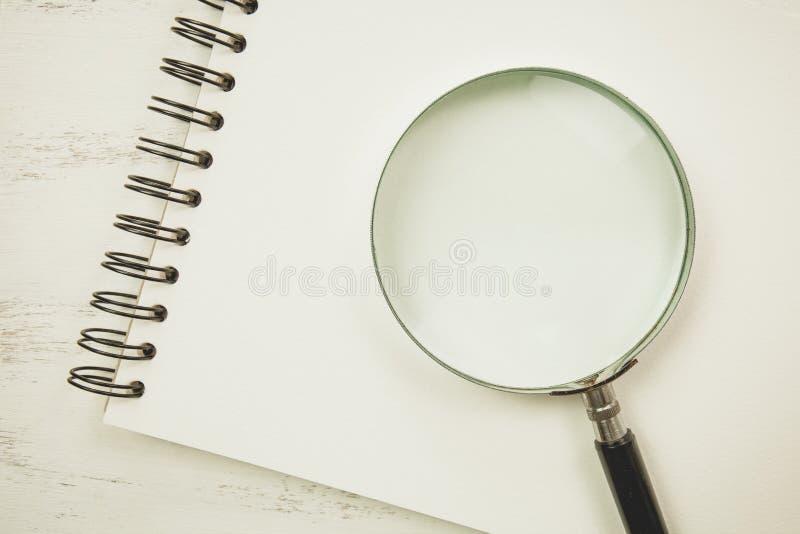 Inte gör de ser smaskiga Anmärkningsbok på den vita tabellen med förstoringsglaset arkivbild