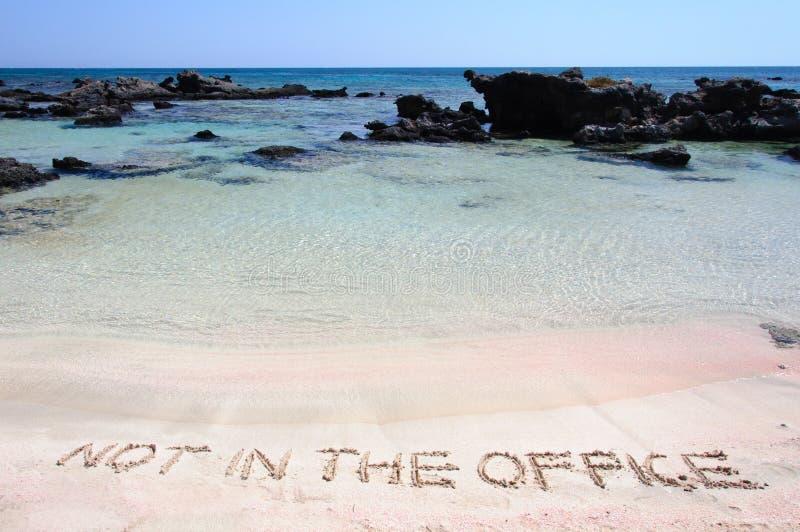 INTE I KONTORET som är skriftligt på sand på en härlig strand, vinkar blått i bakgrund royaltyfri foto
