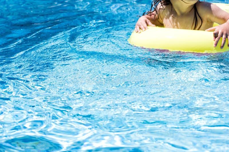 Inte igenkännligt litet barnbarn i en simbassäng fotografering för bildbyråer