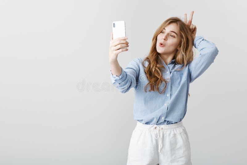 Inte skamset att vara roligt framme av kamera Snygg positiv kvinnlig flicka med blont hår i den blåa blusen som tar fotografering för bildbyråer