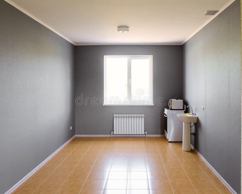 Inte utrustat tomt kökrum med det ljusa fönstret arkivbilder