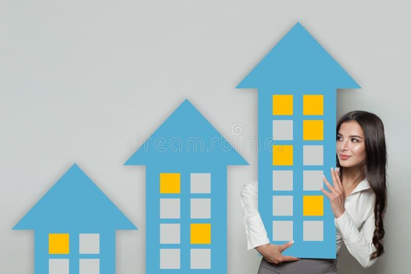 Inteckna, egenskapsinvesteringen och konstruktionsbegreppet Affärskvinnan intecknar mäklaren eller fastighetsmäklare med hus royaltyfri foto