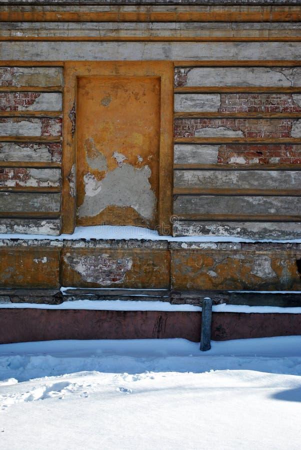 Intecknat fönster av den gamla tegelstenbyggnaden med sprucken murbruk, snöig gata för vinter arkivbild