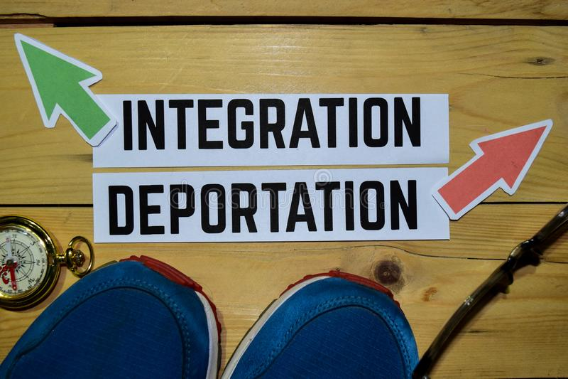 Integração ou deporta16cao oposto aos sinais de sentido com sapatilhas, monóculos e compasso em de madeira foto de stock
