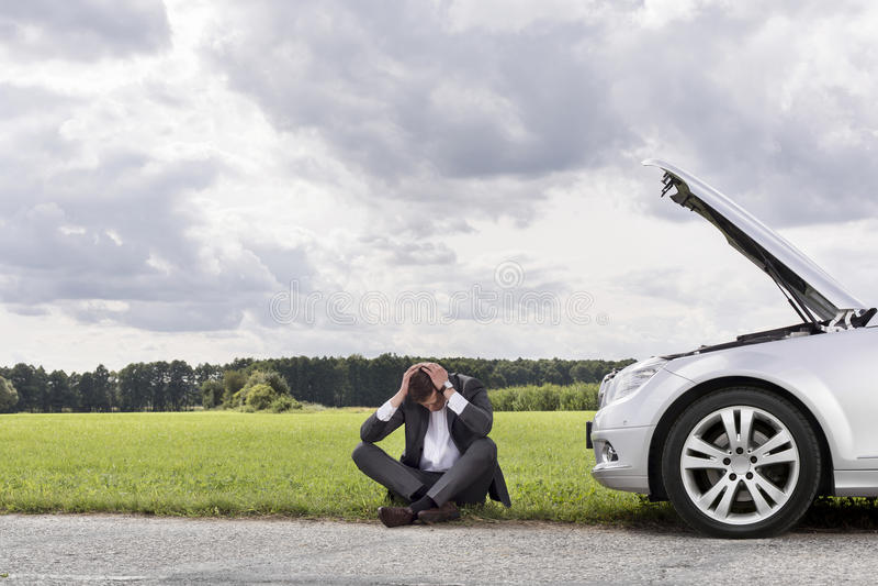 Integral de hombre de negocios con las manos en la cabeza que se sienta en coche analizado en el campo fotos de archivo
