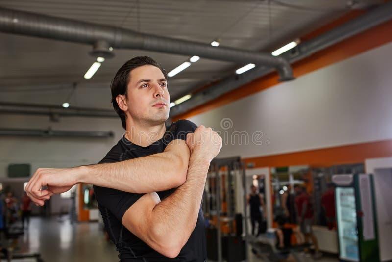 Integral de hombre joven en la ropa de deportes negra que estira su brazo en el gimnasio fotos de archivo
