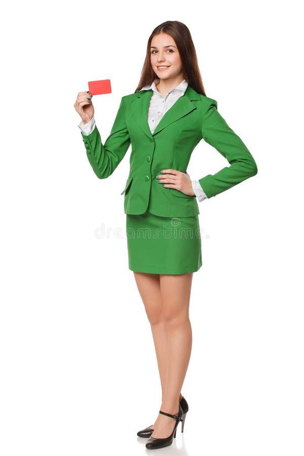 Integral de la mujer de negocios sonriente que muestra la tarjeta del crédito en blanco en traje verde, aislado sobre el fondo bl imagen de archivo