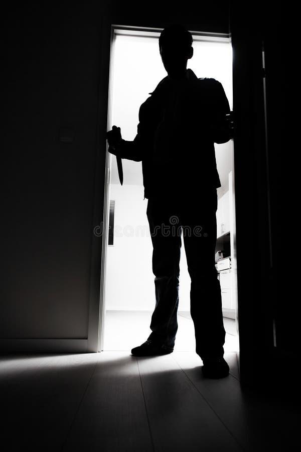 Integral de ladrón con el cuchillo que entra en sitio oscuro imagenes de archivo