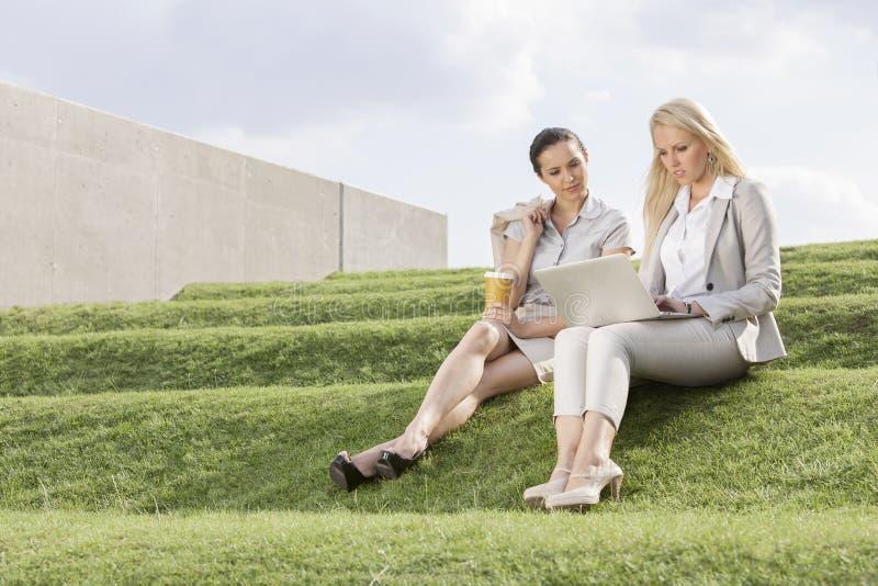 Integral de las empresarias serias que miran el ordenador portátil mientras que se sienta en hierba camina contra el cielo fotografía de archivo libre de regalías