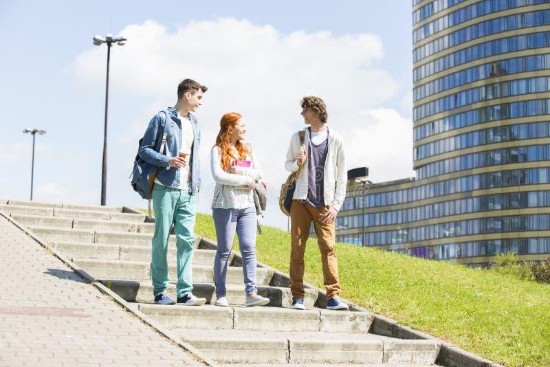 Integral de los amigos jovenes de la universidad que caminan abajo al aire libre fotos de archivo