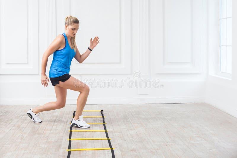 Integral de mujer rubia atlética joven hermosa deportiva en pantalones cortos negros y del top azul sea difícilmente de trabajo y foto de archivo libre de regalías