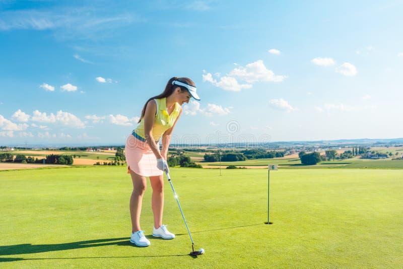 Integral de una mujer atractiva que detiene a un club de golf antes de golpear la bola imagen de archivo