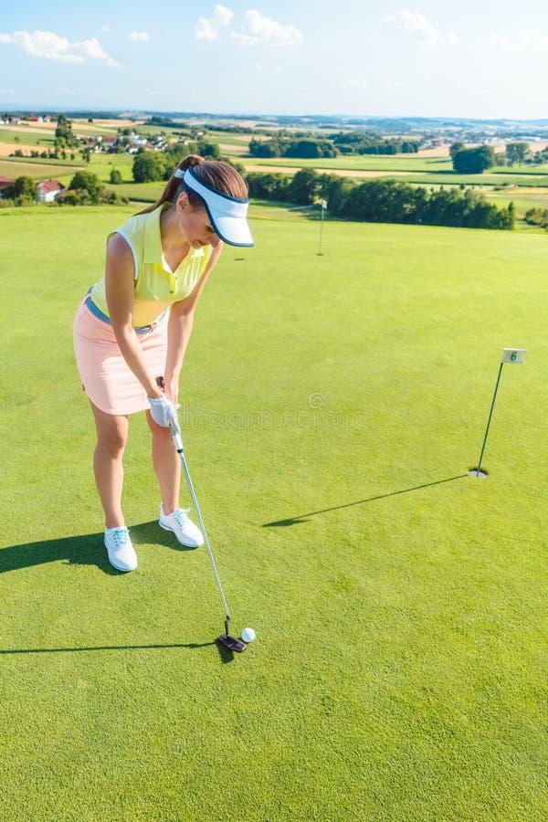 Integral de una mujer atractiva que detiene a un club de golf antes de golpear la bola imagen de archivo libre de regalías