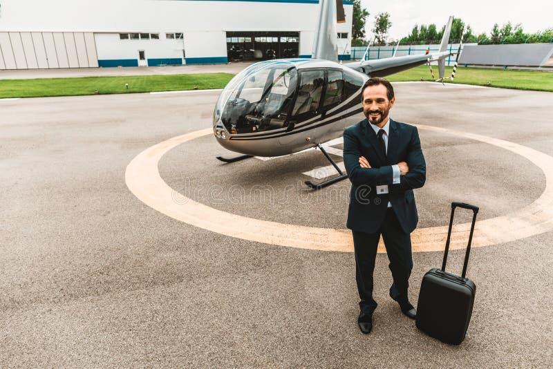 Integral del hombre de negocios feliz que sonríe y que espera su vuelo imagenes de archivo