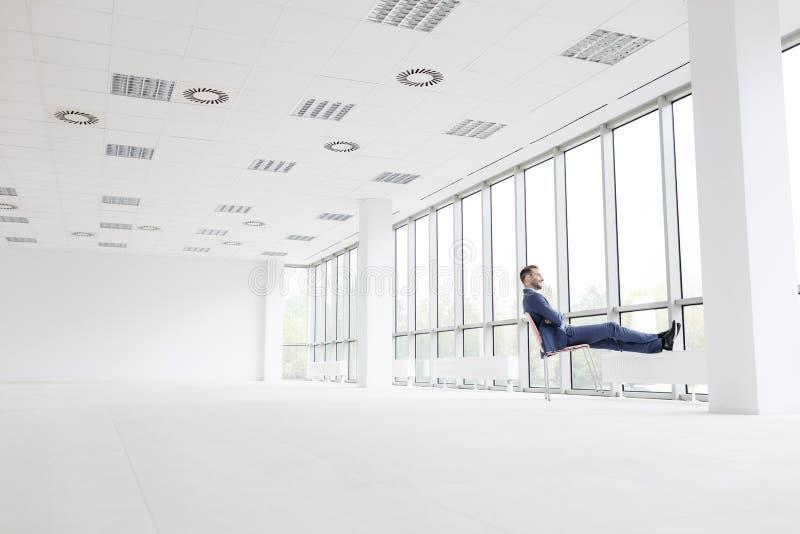 Integral del hombre de negocios joven pensativo que se relaja en silla mientras que mira a través de ventana la nueva oficina vac imagen de archivo libre de regalías