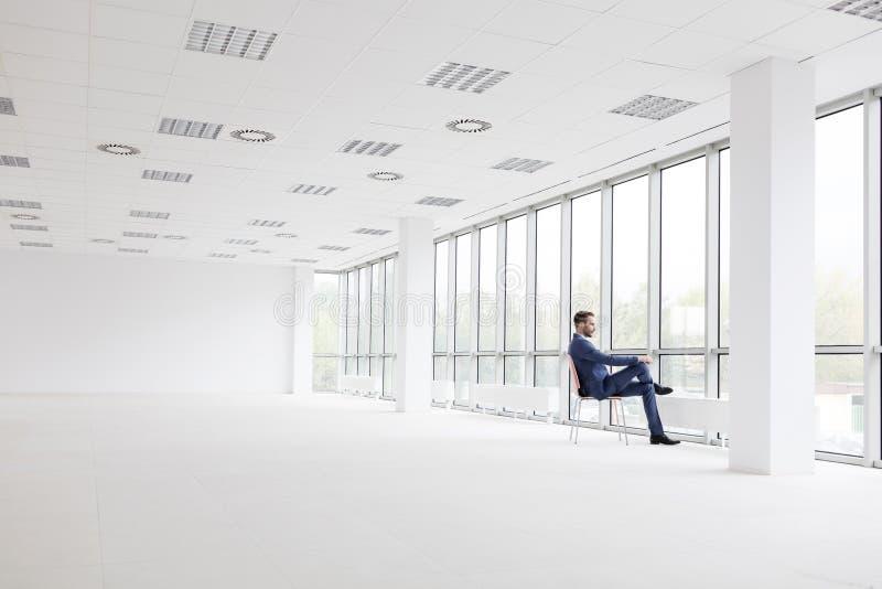 Integral del hombre de negocios joven pensativo que se sienta en silla mientras que mira a través de ventana la nueva oficina vac fotografía de archivo