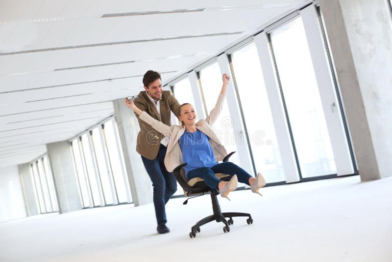 Integral del hombre de negocios joven que empuja al colega femenino en silla en la oficina vacía imagenes de archivo