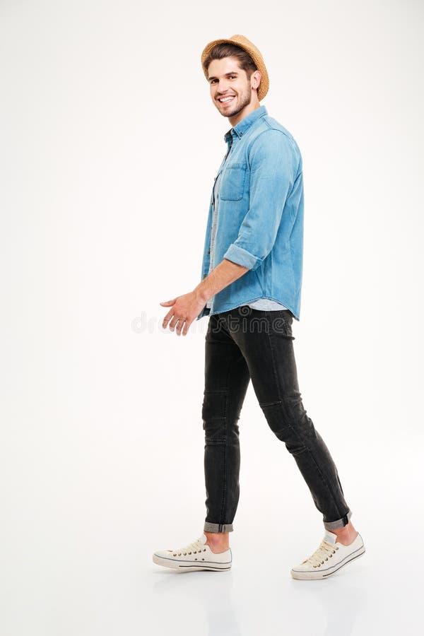 Integral del hombre joven alegre que camina y que sonríe foto de archivo libre de regalías
