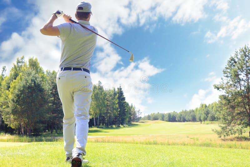 Integral del jugador de golf que juega a golf el d?a soleado Golfista de sexo masculino profesional que toma el tiro en campo de  imagen de archivo