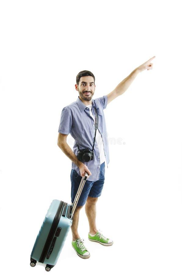Integral del turista masculino joven que se coloca con la maleta, señalando al lado imagen de archivo