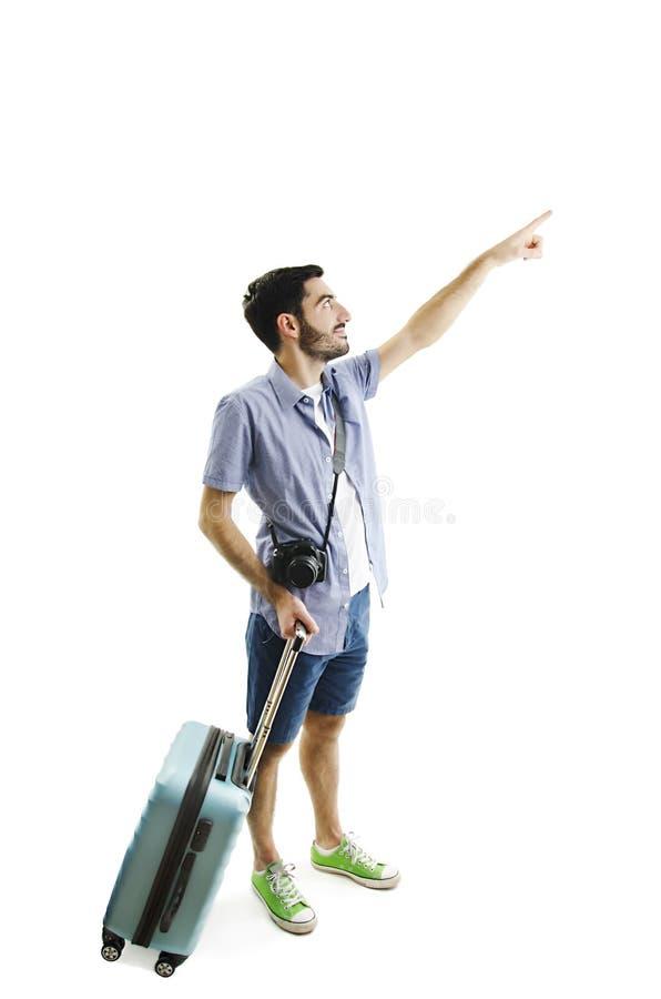 Integral del turista masculino joven que se coloca con la maleta, señalando al lado imágenes de archivo libres de regalías