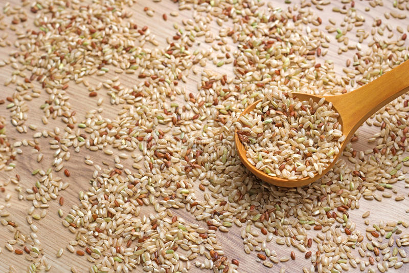 Integral rice in a wooden spoon and spilled grains around. Brown rice in a large spoon and spilled grains Backdrop of rice Top view. Background Integral food royalty free stock images