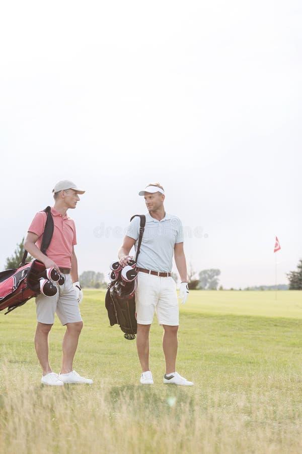 Integrale degli uomini che conversano al campo da golf contro il chiaro cielo fotografia stock libera da diritti