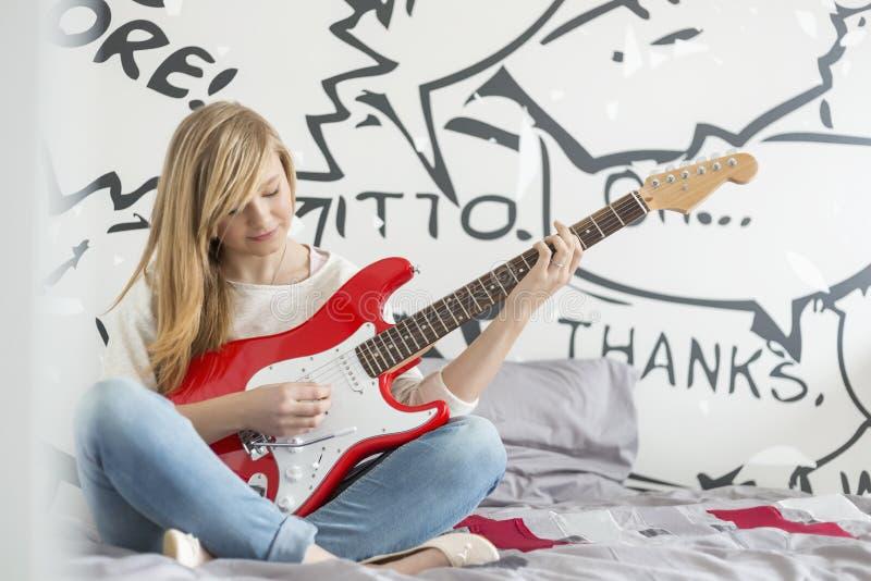 Integrale dell'adolescente che gioca chitarra in camera da letto immagini stock