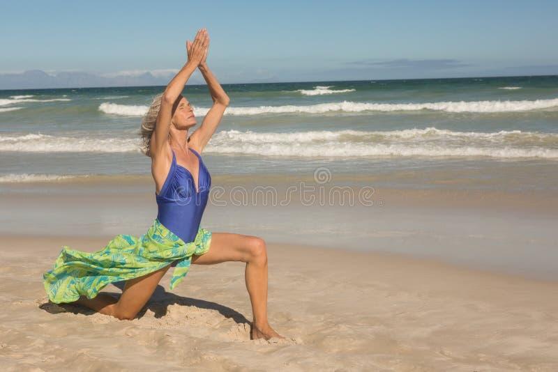 Integrale della donna senior con le armi si è alzato sulla sabbia fotografie stock