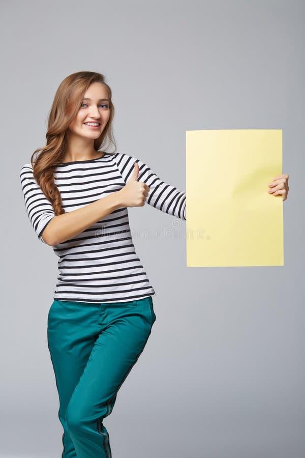 Integrale di bella donna che sta dietro, tenendo annuncio in bianco immagine stock libera da diritti