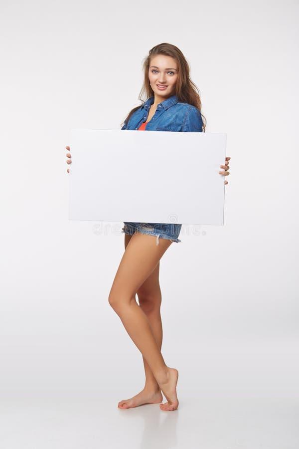 Integrale di bella donna che sta dietro, tenendo bl bianco fotografie stock