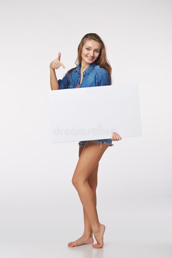 Integrale di bella donna che sta dietro, tenendo bl bianco fotografia stock