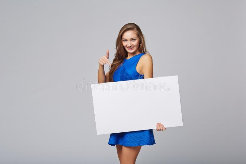 Integrale di bella donna che sta dietro, tenendo bl bianco immagine stock libera da diritti