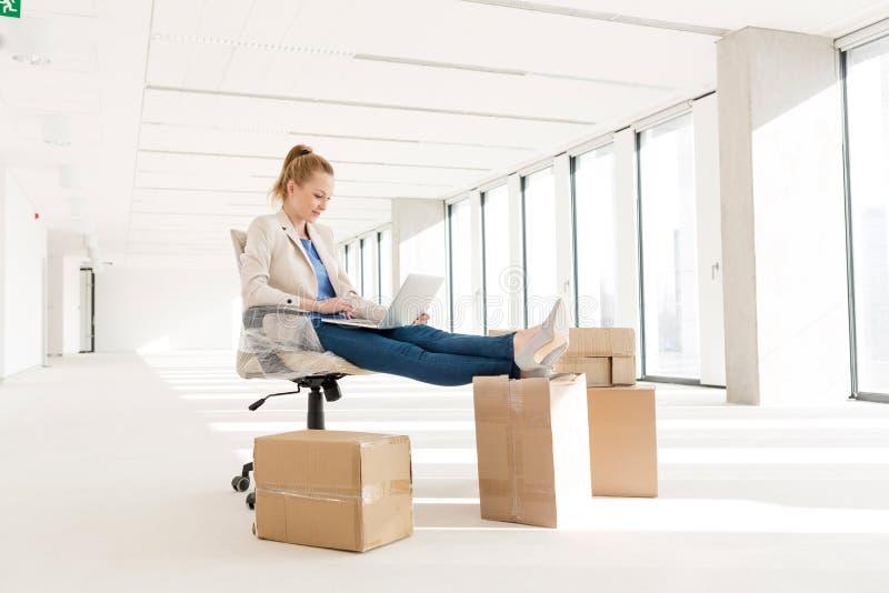 Integrale di giovane donna di affari che utilizza computer portatile con i piedi su sulla scatola di cartone nel nuovo ufficio immagine stock libera da diritti